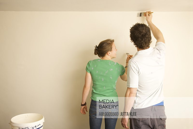 Back view of a couple painting a wall