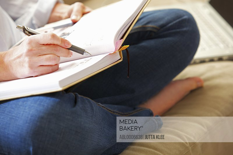 Woman Sitting Cross Legged Writing on Note Pad, Close-up view