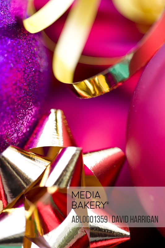 Extreme close up of red and purple Christmas baubles and a gold bow and ribbon
