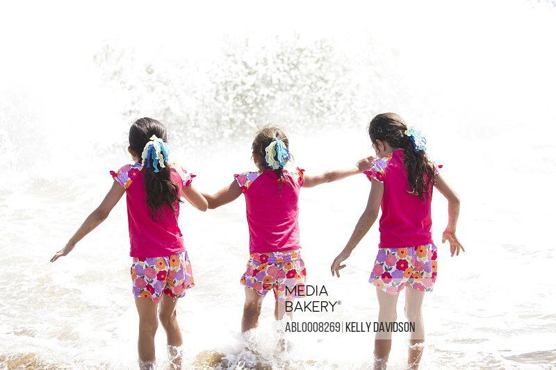 Back View of Girls in Matching Outfit Walking into the Sea