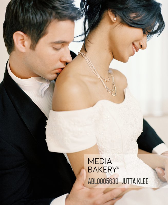 Bridegroom kissing a bride shoulder