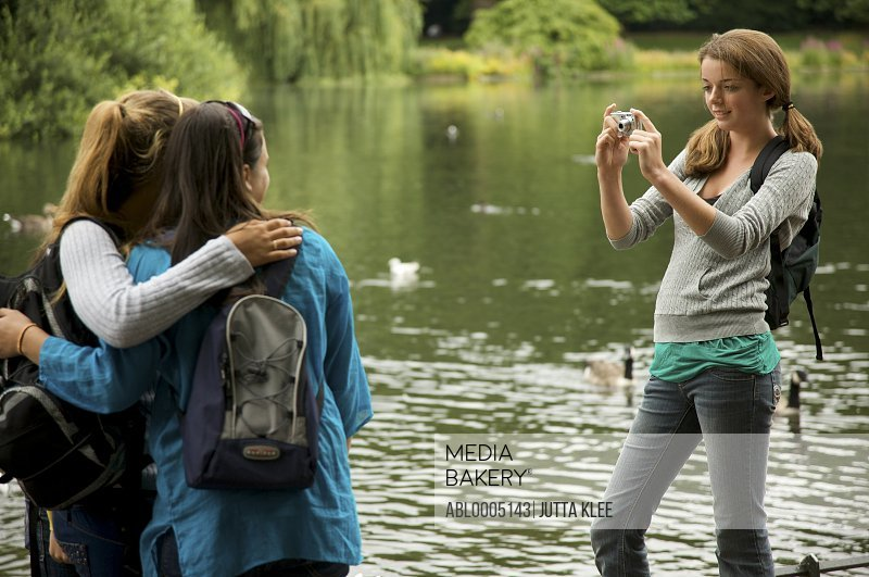 Teenaged girl taking photograph of two women by a lake