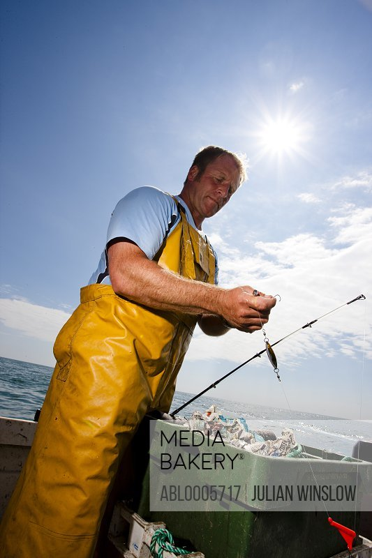 Portrait of a fisherman standing in a boat adjusting a fishing rod