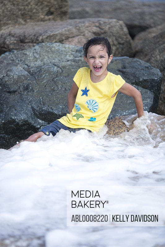 Girl Sitting on Rocks Playing in Sea Waves