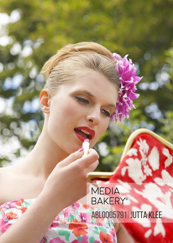 Woman applying lipstick whilst holding her handbag