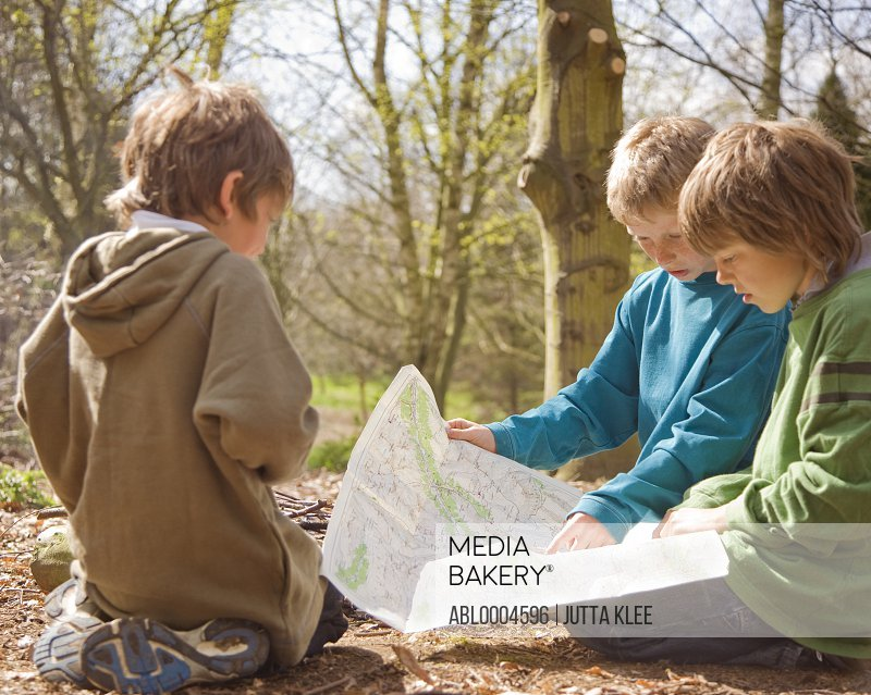 Three boys kneeling around campfire looking at map