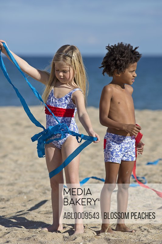 Boy and Girl Playing with Ribbons on Beach