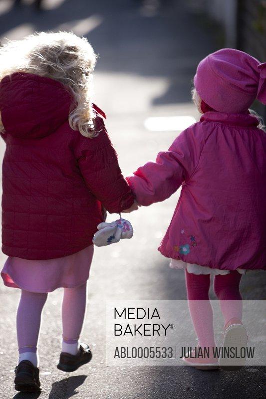 Back view of two little girls walking on a street