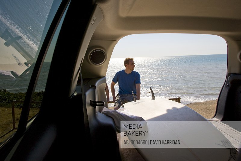 Portrait of a man sitting with his back to the ocean shot from inside car