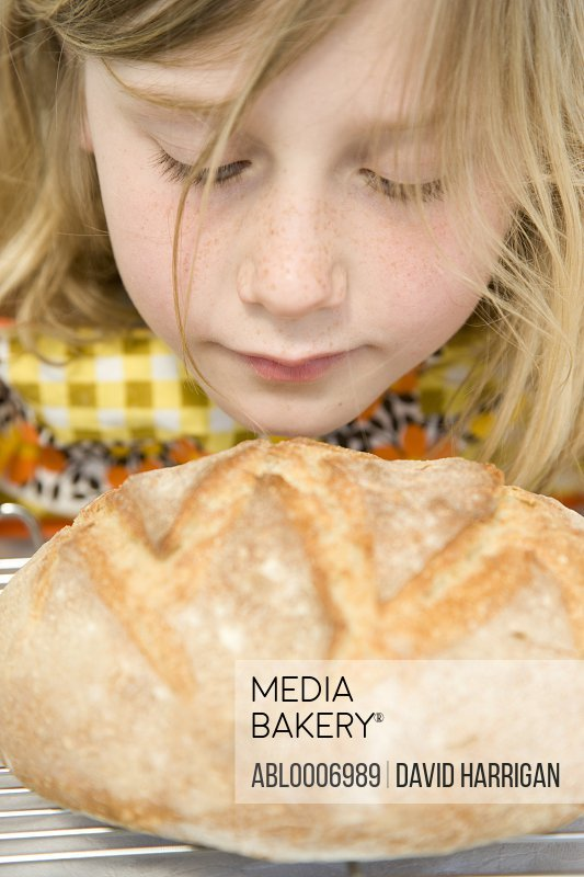 Young Girl Smelling a Loaf of Bread