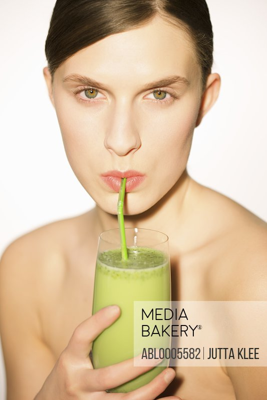 Woman drinking a vegetable smoothie with a straw