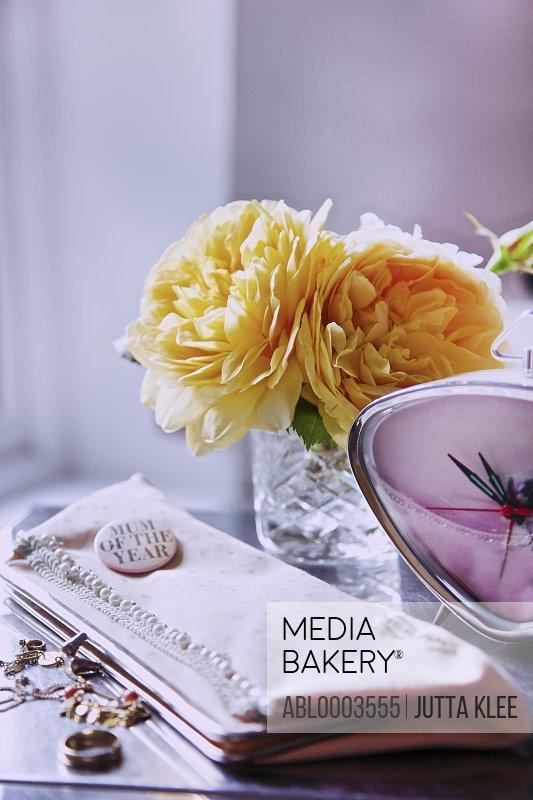 Handbag, Clock, Jewellery and Flowers on Woman's Dressing Table