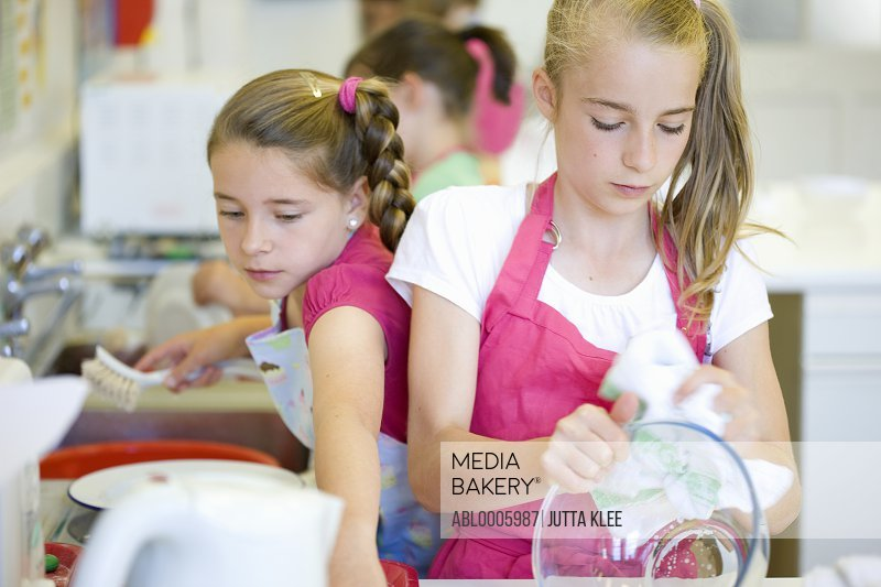 Young girls in cookery class washing up