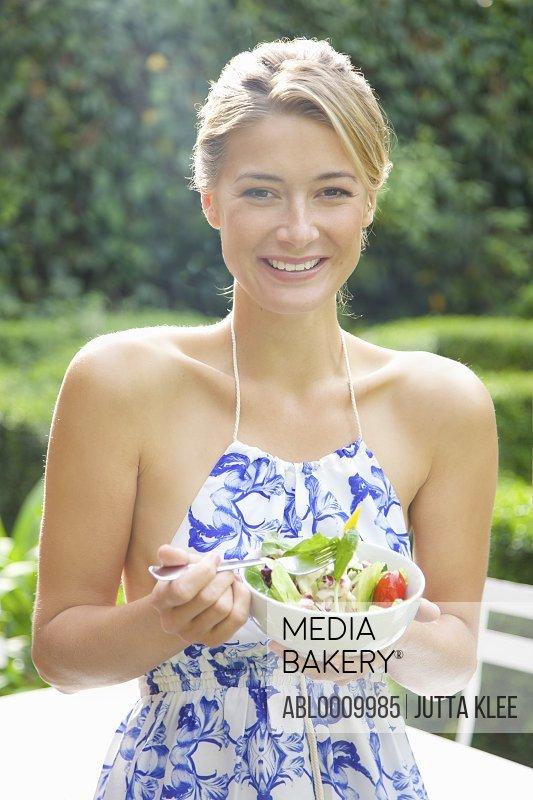 Woman Eating Salad in Garden Smiling