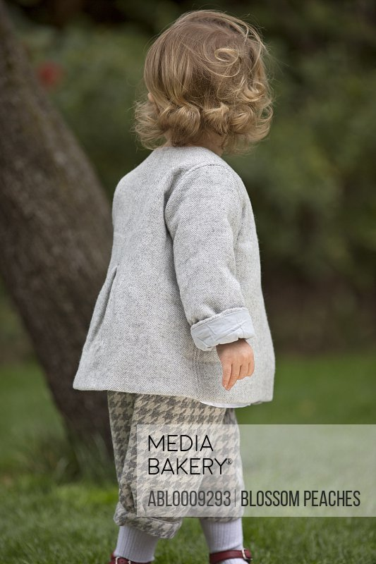 Back View of Young Girl Walking in Garden
