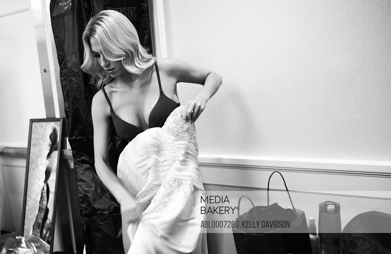 Woman Changing Into Evening Gown in Dressing Room