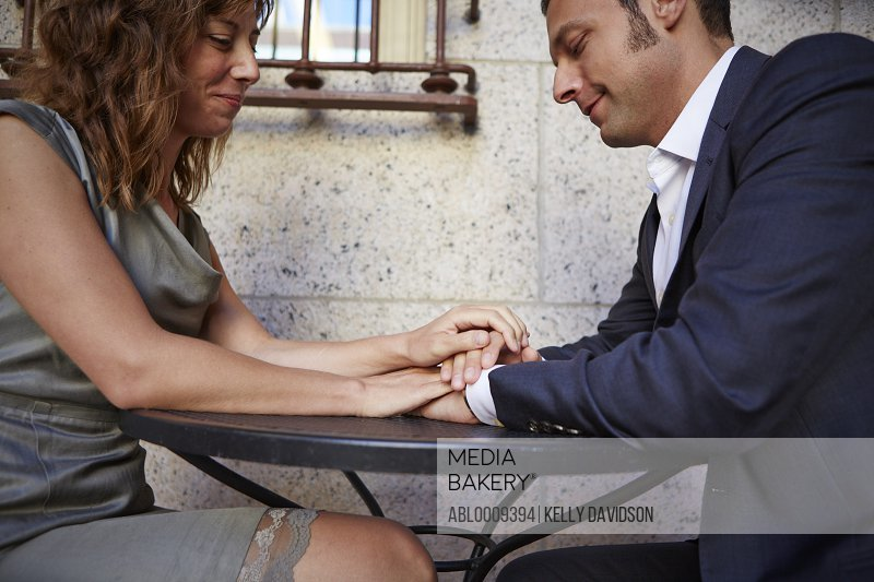 Couple Sitting at Outdoor Table Holding Hands