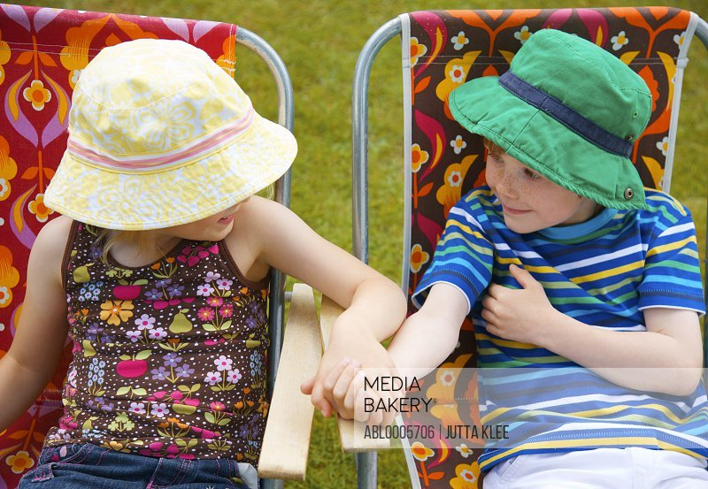 Boy and girl sitting on folding chairs arm wrestling