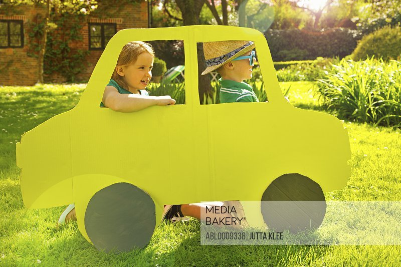 Boy and Girl Kneeling behind Cardboard Cut Out in Shape of Car