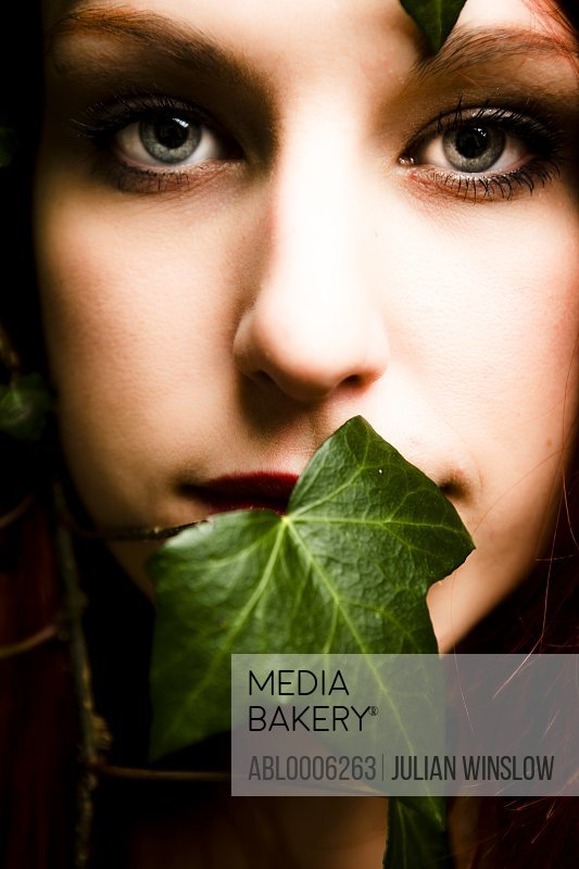 Close up of a woman's face with ivy leaf covering her mouth