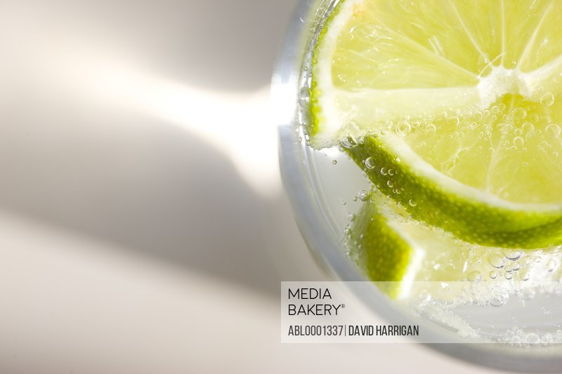 Extreme close up of a glass of sparkling water with sliced lime - high angle