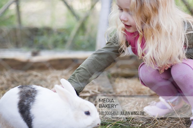 Little girl crouching and caressing a rabbit