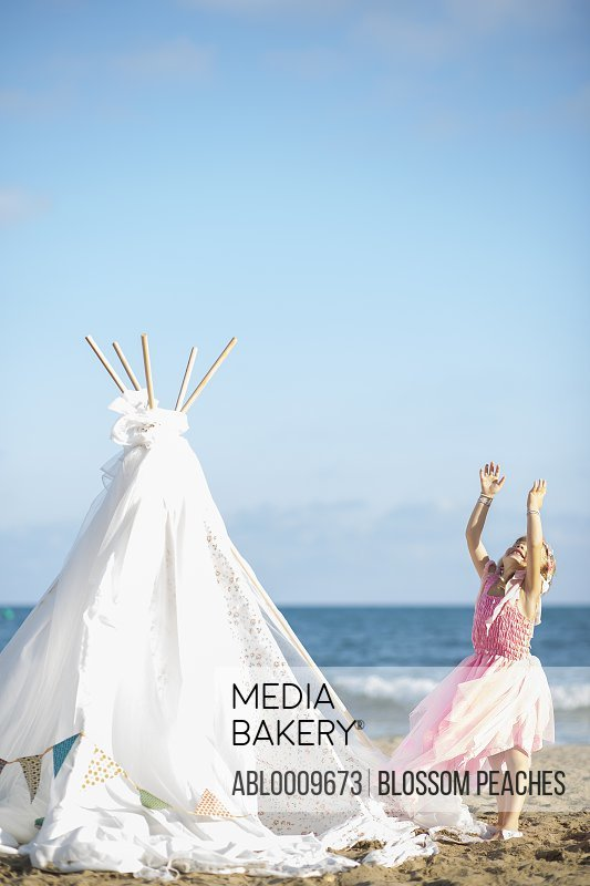 Young Girl in Fancy Dress Playing on Beach next to Teepee