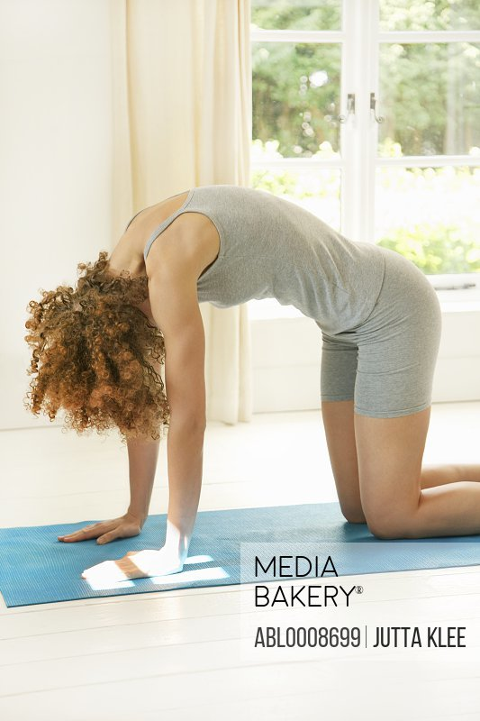 Woman Practicing Yoga in the Cat Pose