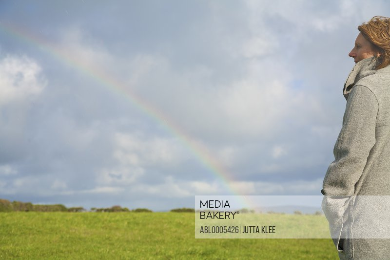 Woman standing in a field looking at the rainbow