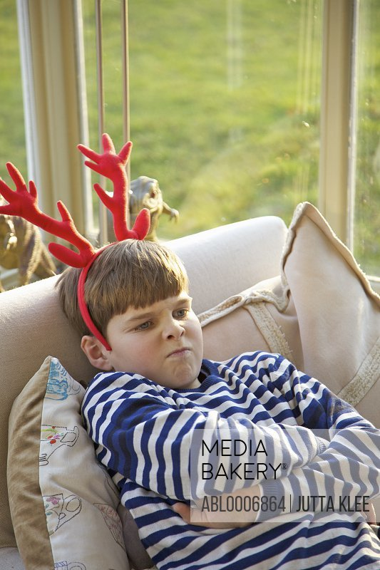 Boy Wearing Christmas Antlers Pulling Faces