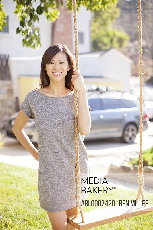 Smiling Woman Standing by Swing