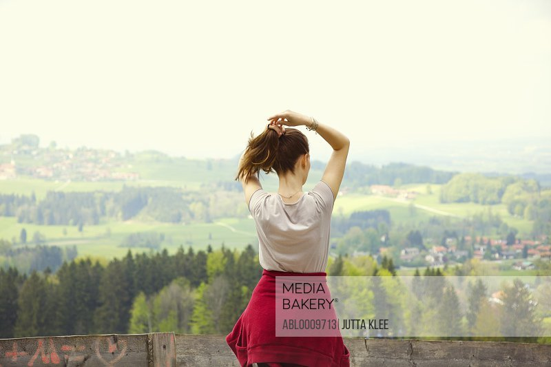 Back View of Young Woman Adjusting Hair Looking at Landscape