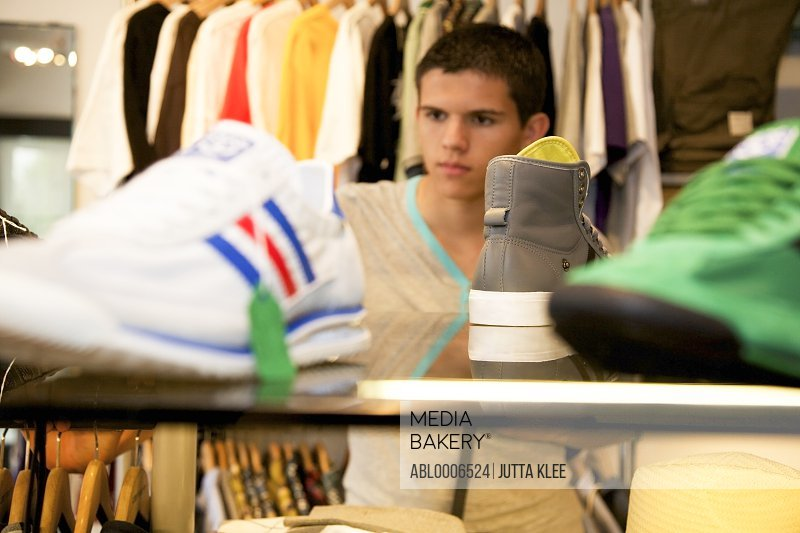 Teenage Boy Browsing in Clothing Store
