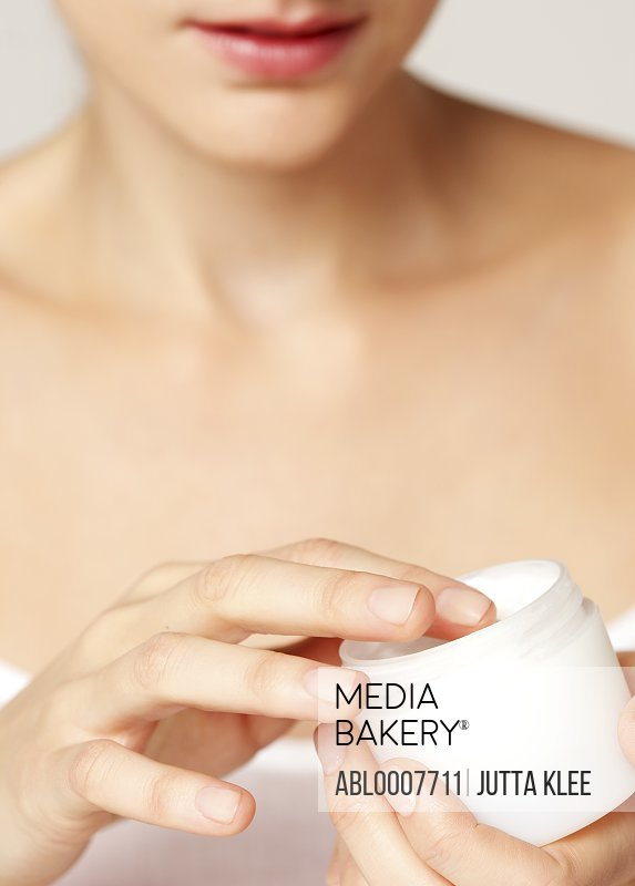 Woman Holding an Open Jar of Cosmetic Cream