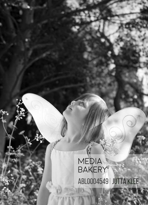 Portrait of a young girl in a fairy costume standing in a garden looking up