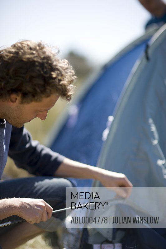 Close up of young man inserting tent pole into tent
