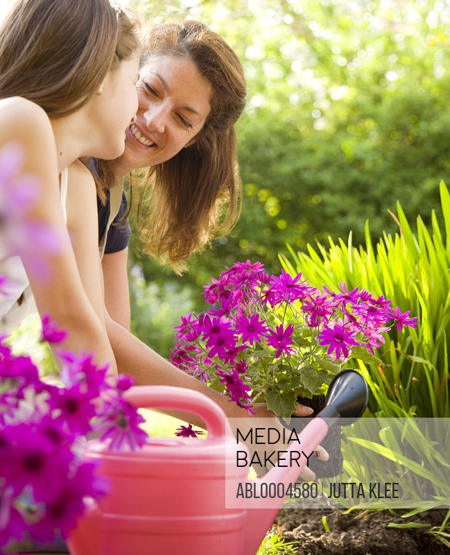 Mother and daughter kneeling in the garden tending plants and smiling