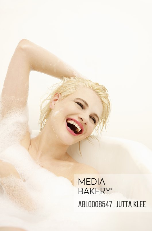 Smiling Young Woman Having a Bath