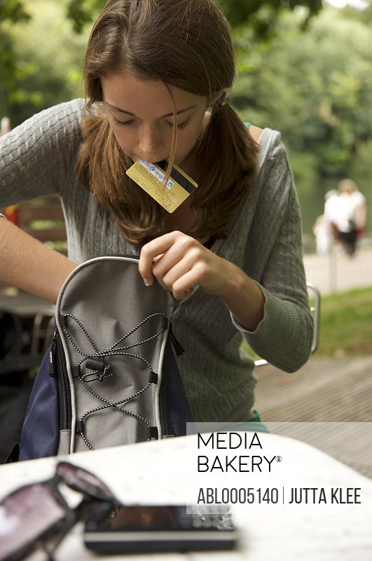 Teenaged girl holding a credit card in her mouth looking for something in her rucksack
