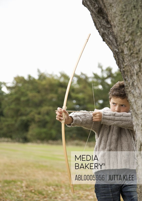 Young boy standing by a tree aiming with a bow and arrow