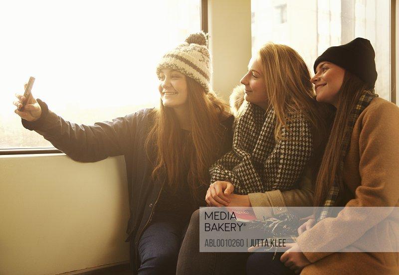Teenage Girls Sitting on Train Taking Selfie