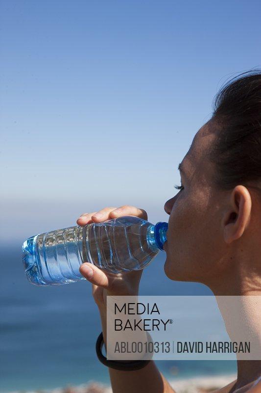 Woman Drinking Water from Bottle by Ocean