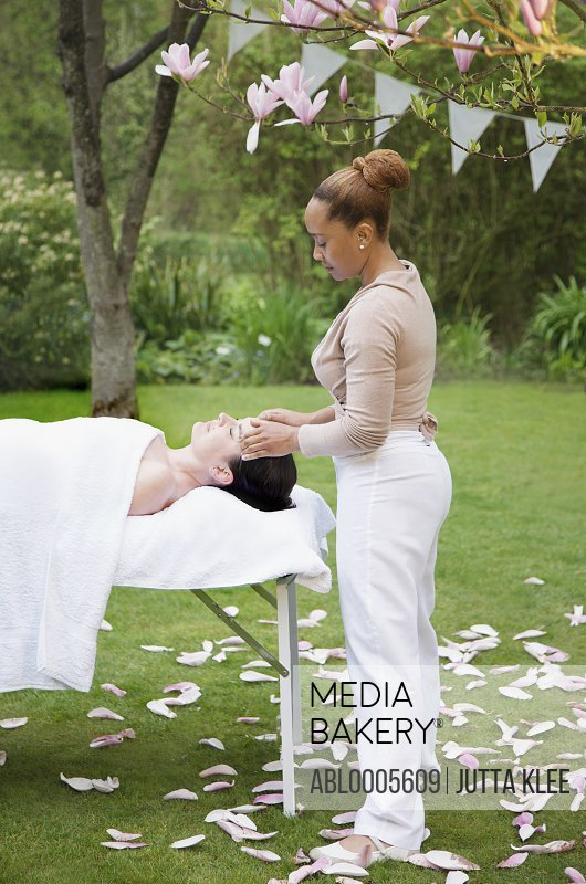 Masseuse giving a woman a facial massage under a magnolia tree