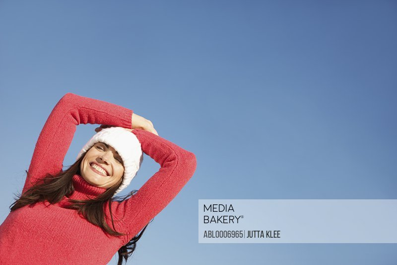 Woman with Hands on Head against Blue Sky, Low angle view