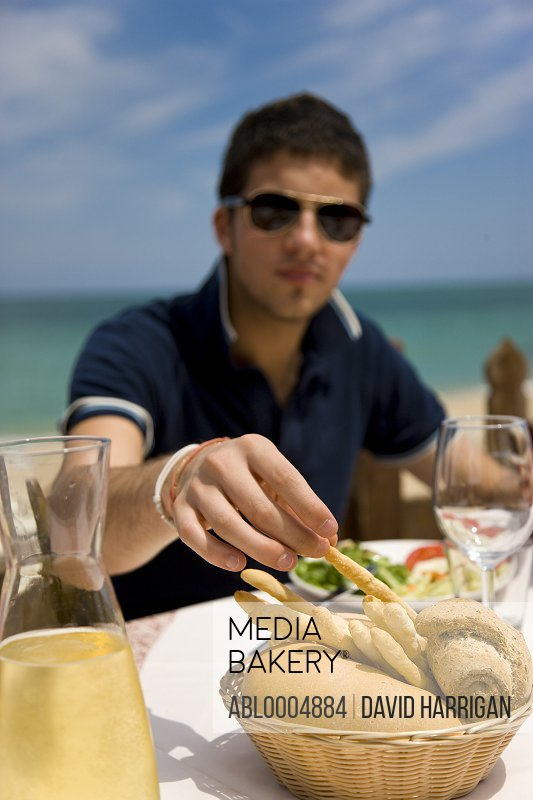 Young man eating al fresco by the sea picking up a breadstick from bread basket