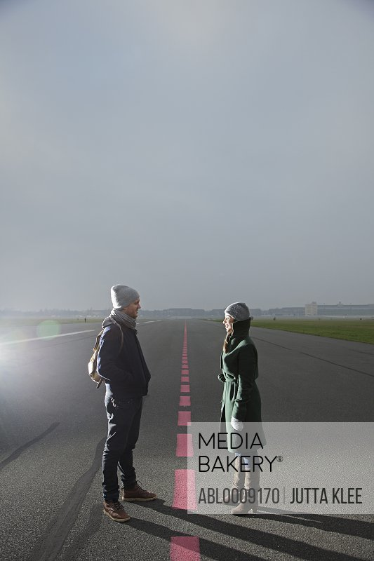Couple Standing on Airport Runway Facing each other