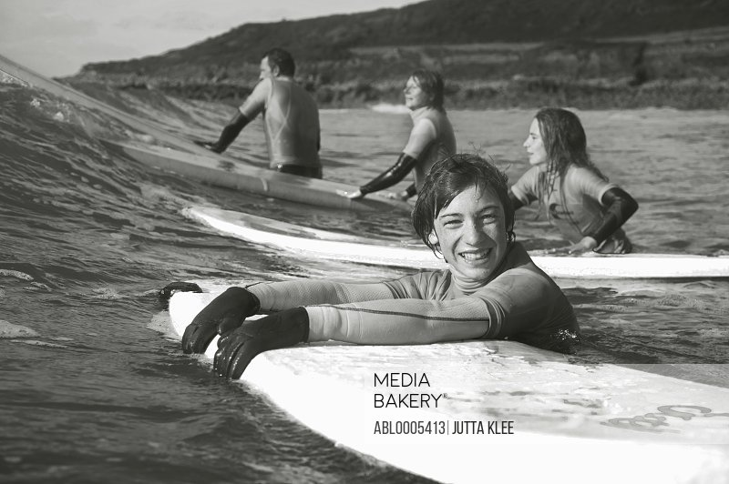 Smiling teenaged boy in the sea holding on to his surfboard