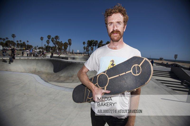 Man Holding Skateboard in Skate Park