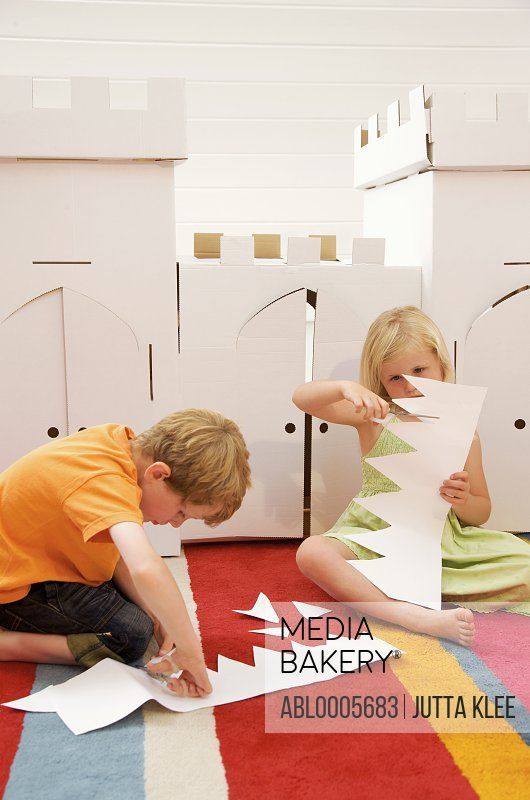 Boy and girl sitting in front of a cardboard castle cutting paper