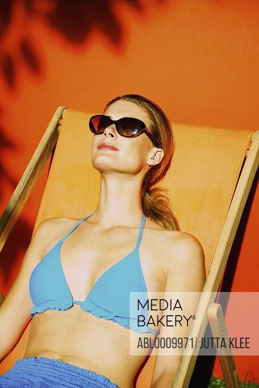 Woman Sunbathing on Orange Deck Chair